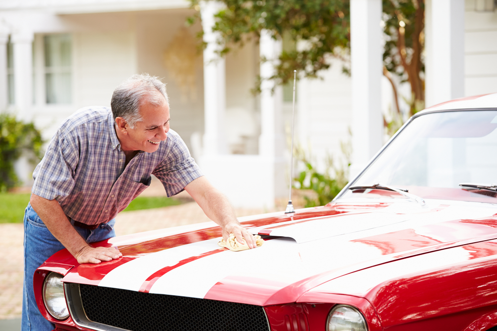 Older Gentleman washing a restored, red car